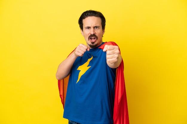 Jeune homme caucasien isolé sur fond jaune en costume de super-héros et combats