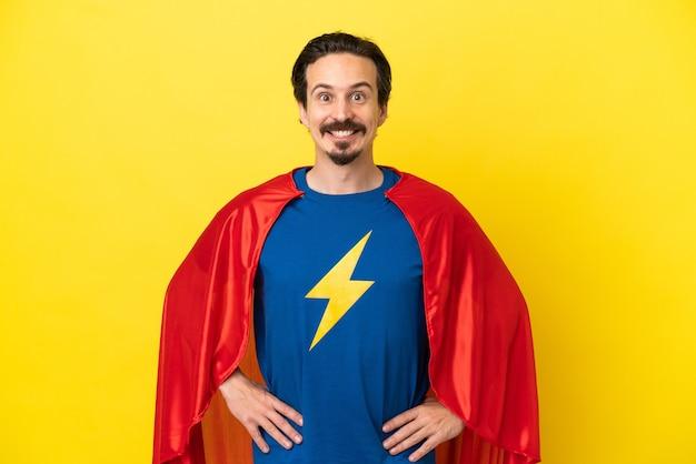 Jeune homme caucasien isolé sur fond jaune en costume de super-héros posant avec les bras à la hanche et souriant