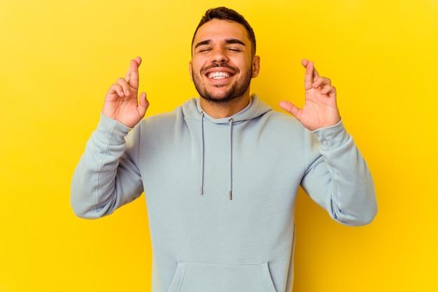 Jeune homme caucasien isolé sur fond jaune croisant les doigts pour avoir de la chance