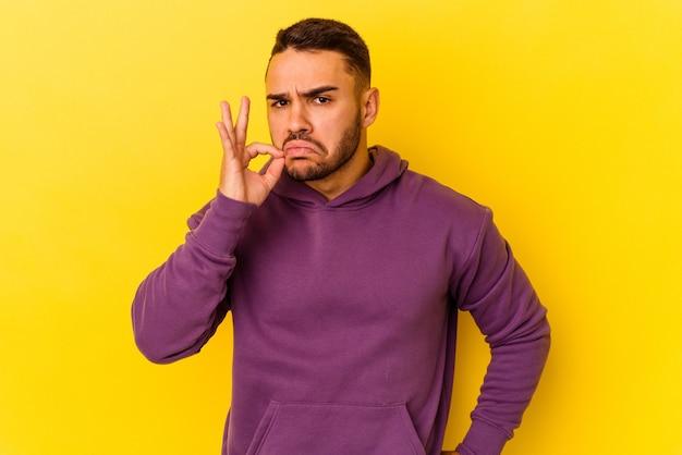 Jeune homme caucasien isolé sur fond jaune avec les doigts sur les lèvres gardant un secret.