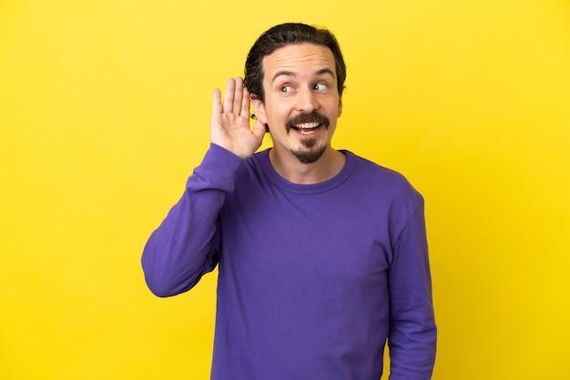 Jeune homme caucasien isolé sur fond jaune écoutant quelque chose en mettant la main sur l'oreille