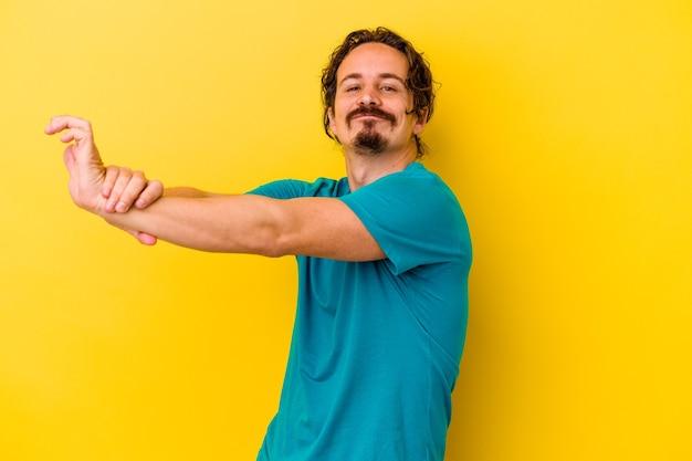 Jeune homme caucasien isolé sur fond jaune, étirement des bras, position détendue.