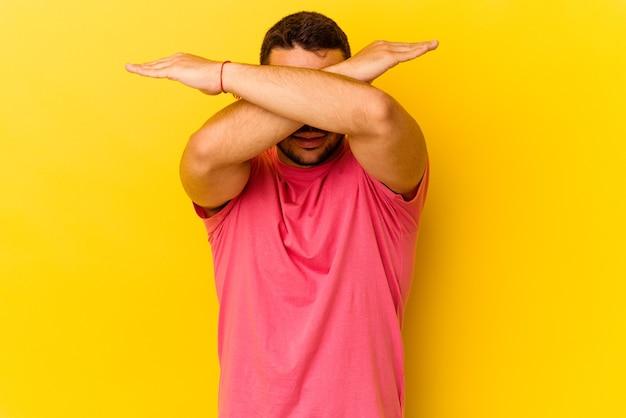 Jeune homme caucasien isolé sur fond jaune gardant deux bras croisés, concept de déni.