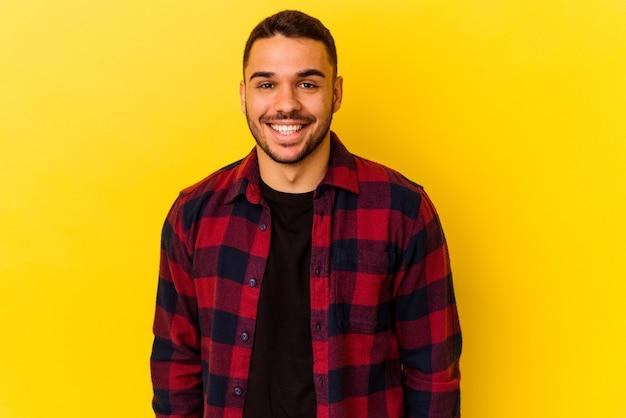 Jeune homme caucasien isolé sur fond jaune heureux, souriant et joyeux.