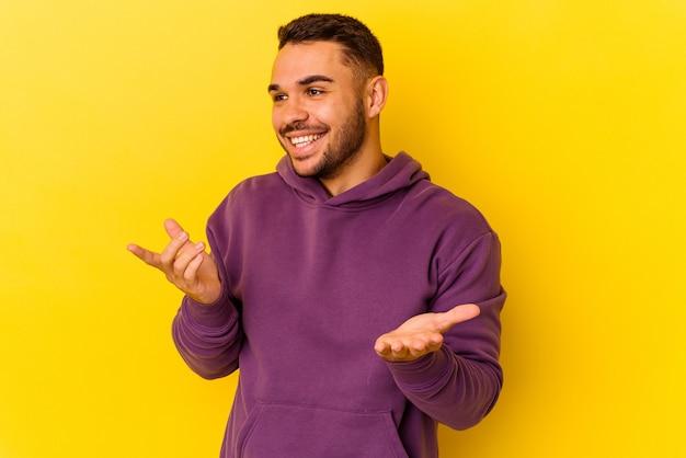 Jeune homme caucasien isolé sur fond jaune joyeux riant beaucoup. notion de bonheur.
