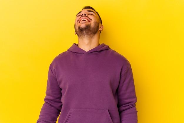 Jeune homme caucasien isolé sur fond jaune riant détendu et heureux, cou tendu montrant les dents.