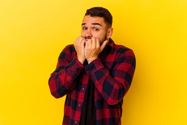Jeune homme caucasien isolé sur fond jaune se rongeant les ongles, nerveux et très anxieux.
