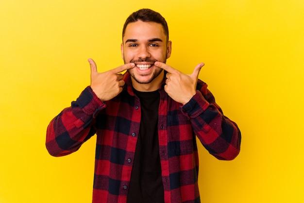 Jeune homme caucasien isolé sur fond jaune sourit, pointant du doigt la bouche.