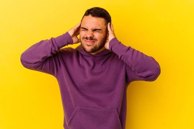 Jeune homme caucasien isolé sur fond jaune touchant les temples et ayant des maux de tête.