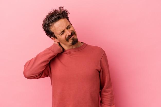 Jeune homme caucasien isolé sur fond rose ayant une douleur au cou due au stress, en le massant et en le touchant avec la main.