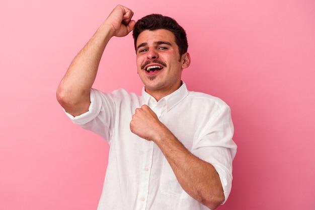 Jeune homme caucasien isolé sur fond rose célébrant une journée spéciale, saute et lève les bras avec énergie.
