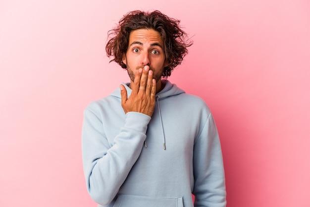 Jeune homme caucasien isolé sur fond rose choqué, se couvrant la bouche avec les mains, impatient de découvrir quelque chose de nouveau.