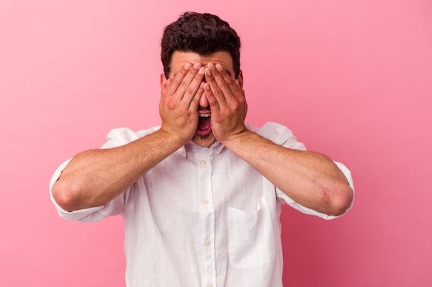 Jeune homme caucasien isolé sur fond rose couvre les yeux avec les mains, sourit largement en attente d'une surprise.