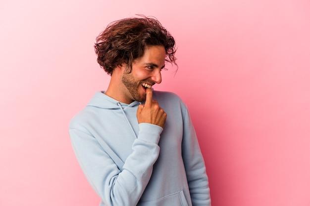 Jeune homme caucasien isolé sur fond rose détendu en pensant à quelque chose en regardant un espace de copie.