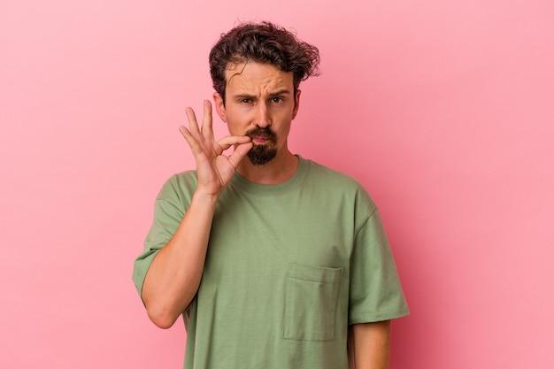 Jeune homme caucasien isolé sur fond rose avec les doigts sur les lèvres gardant un secret.