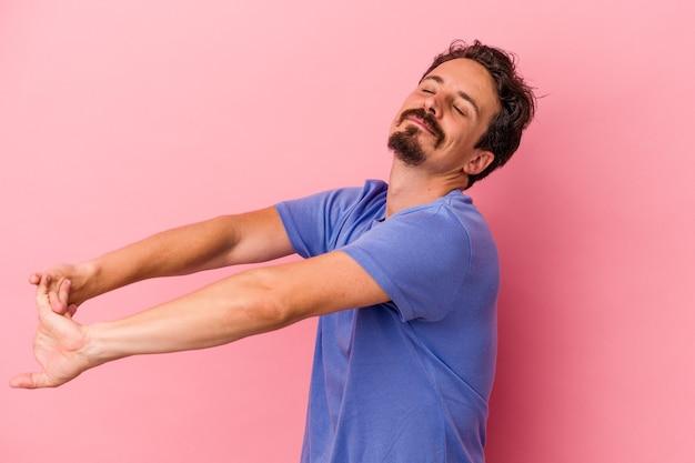 Jeune homme caucasien isolé sur fond rose étirant les bras, position détendue.