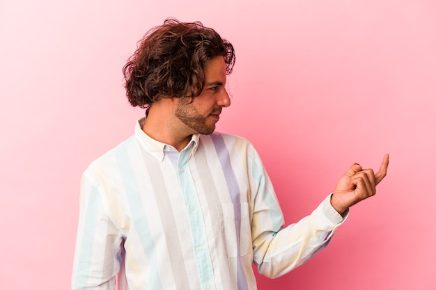 Jeune homme caucasien isolé sur fond rose pointant du doigt vers vous comme s'il vous invitait à vous rapprocher.