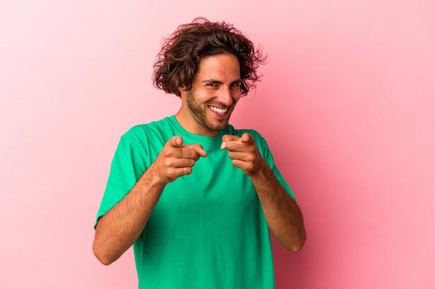 Jeune homme caucasien isolé sur fond rose pointant vers l'avant avec les doigts.