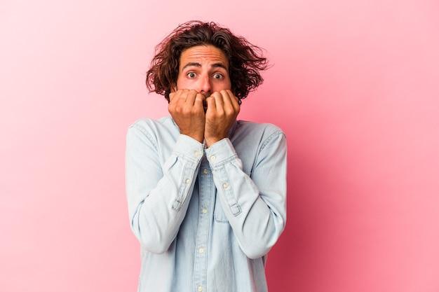 Jeune homme caucasien isolé sur fond rose se rongeant les ongles, nerveux et très anxieux.
