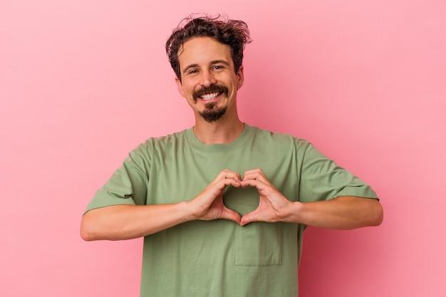 Jeune homme caucasien isolé sur fond rose souriant et montrant une forme de coeur avec les mains.