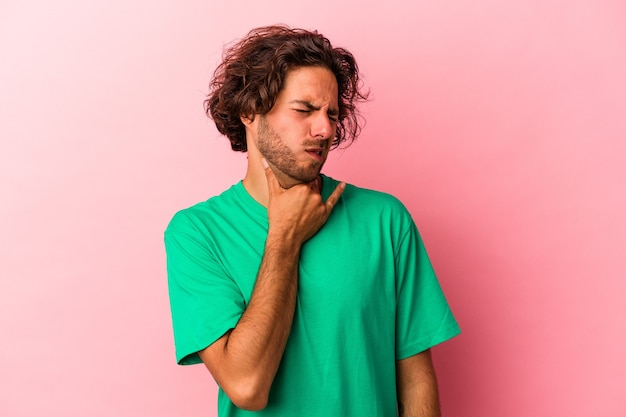 Jeune homme caucasien isolé sur fond rose touchant l'arrière de la tête, pensant et faisant un choix.