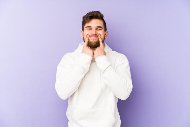 Jeune homme caucasien isolé sur fond violet doutant entre deux options.