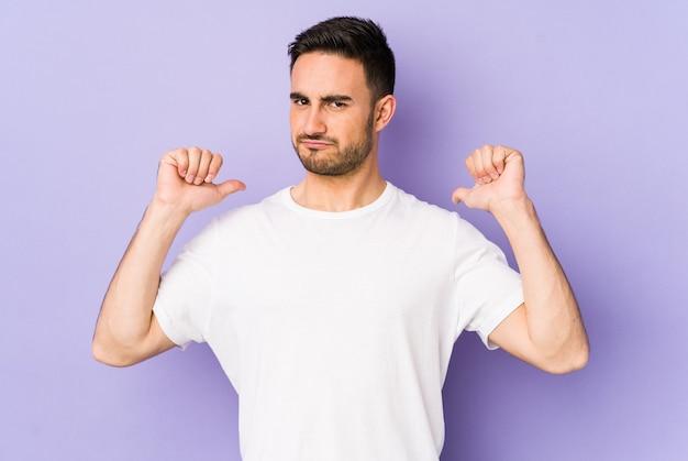 Jeune homme caucasien isolé sur fond violet se sent fier et confiant, exemple à suivre.