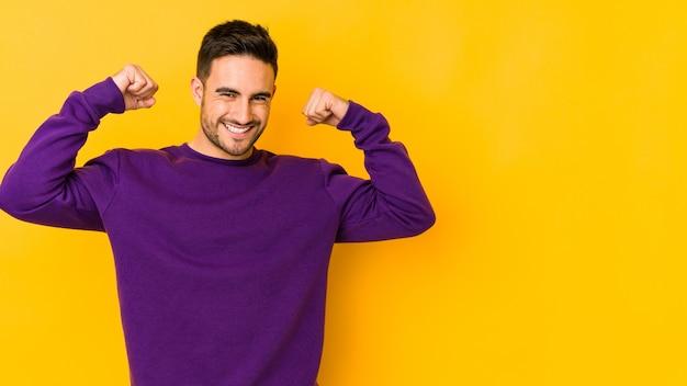 Jeune homme caucasien isolé sur jaune célébrant une journée spéciale, saute et lève les bras avec énergie.