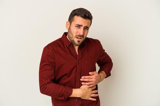 Jeune homme caucasien isolé sur un mur blanc ayant une douleur au foie, mal à l'estomac.
