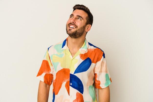 Jeune homme caucasien isolé sur un mur blanc détendu et heureux en riant, cou tendu montrant les dents.