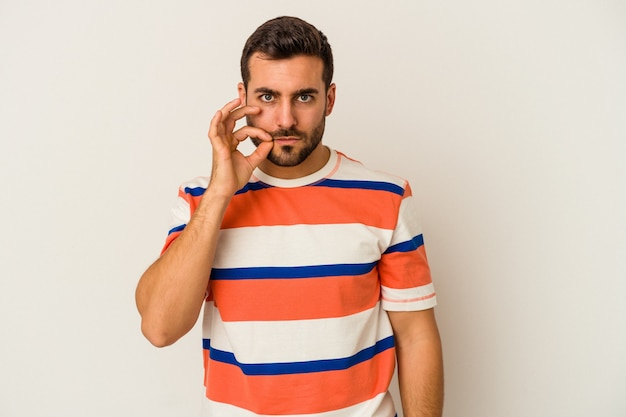 Jeune homme caucasien isolé sur un mur blanc avec les doigts sur les lèvres en gardant un secret.