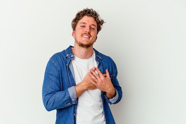 Jeune homme caucasien isolé sur un mur blanc a une expression amicale, appuyant sur la paume de la main contre la poitrine. concept d'amour.
