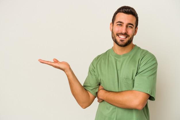 Jeune homme caucasien isolé sur un mur blanc montrant un espace de copie sur une paume et tenant une autre main sur la taille.