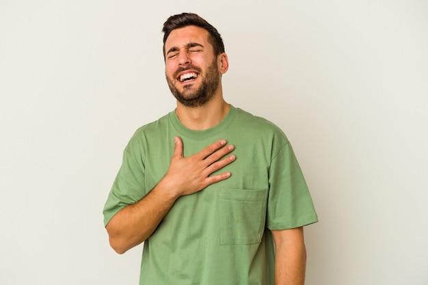 Jeune homme caucasien isolé sur un mur blanc rit bruyamment en gardant la main sur la poitrine.