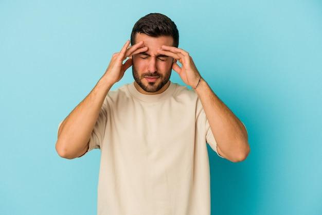 Jeune homme caucasien isolé sur un mur bleu ayant mal à la tête, touchant l'avant du visage.