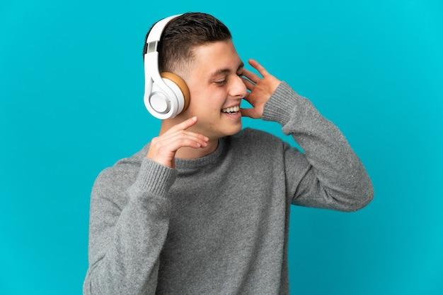 Jeune homme caucasien isolé sur mur bleu écoute de la musique et du chant