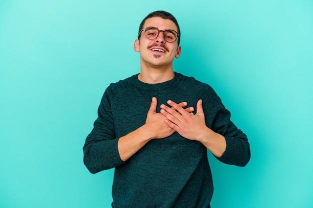 Jeune homme caucasien isolé sur un mur bleu a une expression amicale, en appuyant sur la paume de la main contre la poitrine