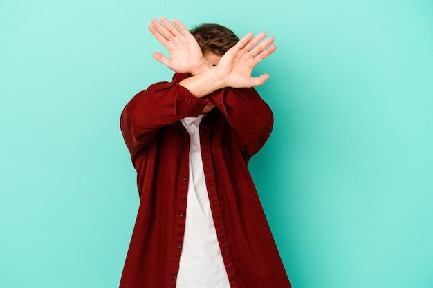 Jeune homme caucasien isolé sur un mur bleu gardant deux bras croisés, concept de déni.