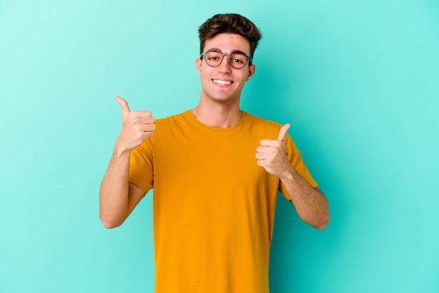 Jeune homme caucasien isolé sur un mur bleu levant les deux pouces vers le haut, souriant et confiant