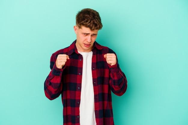 Jeune homme caucasien isolé sur mur bleu montrant le poing à l'avant, expression faciale agressive