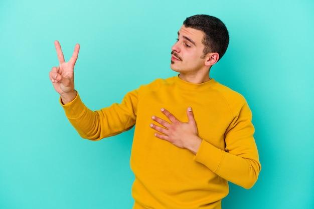 Jeune homme caucasien isolé sur un mur bleu en prêtant serment, mettant la main sur la poitrine
