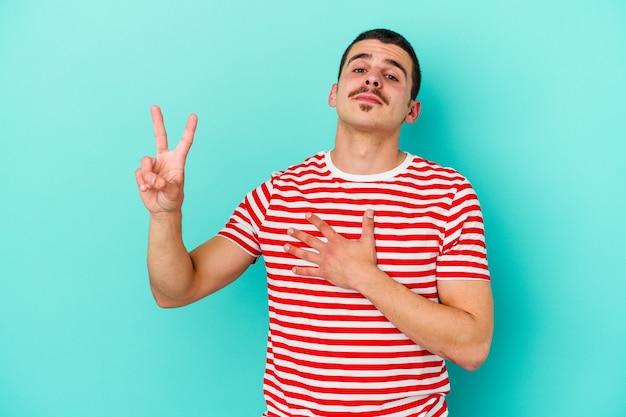 Jeune homme caucasien isolé sur un mur bleu en prêtant serment, mettant la main sur la poitrine.