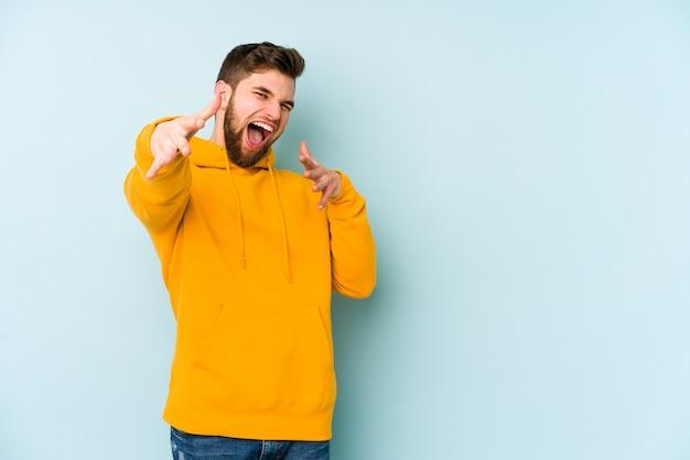 Jeune homme caucasien isolé sur un mur bleu se sent confiant en donnant un câlin à la caméra.