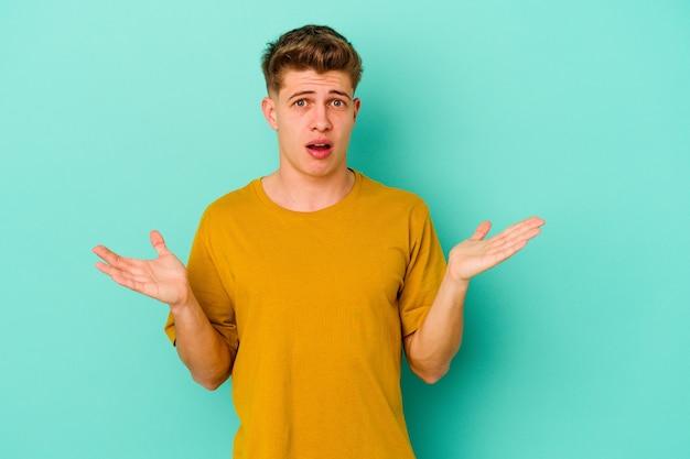Jeune homme caucasien isolé sur un mur bleu surpris et choqué.