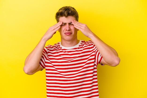 Jeune homme caucasien isolé sur un mur jaune ayant mal à la tête, touchant l'avant du visage.