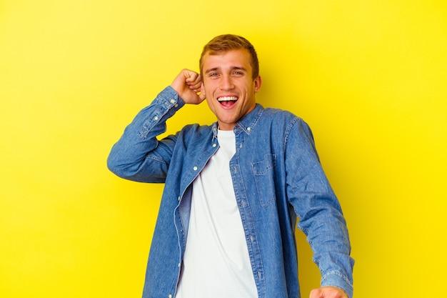 Jeune homme caucasien isolé sur mur jaune dansant et s'amusant.
