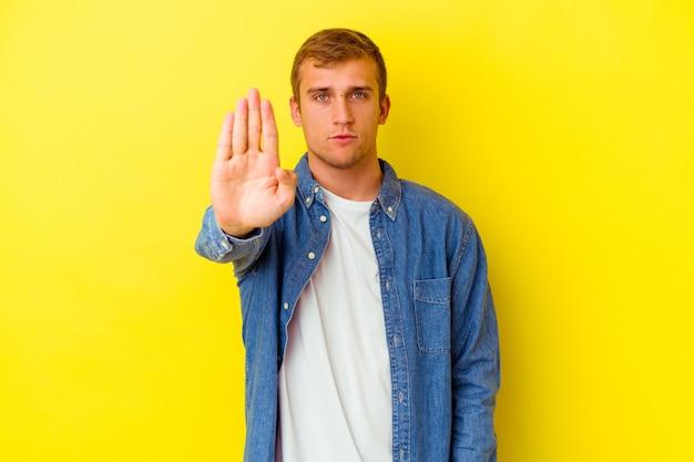 Jeune homme caucasien isolé sur mur jaune debout avec la main tendue montrant le panneau d'arrêt, vous empêchant.