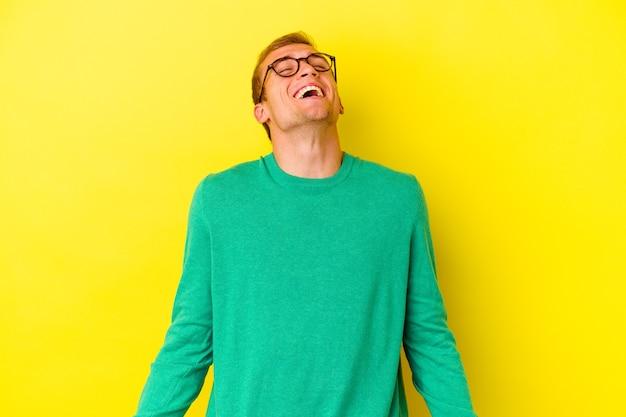Jeune homme caucasien isolé sur un mur jaune détendu et heureux en riant, cou tendu montrant les dents.