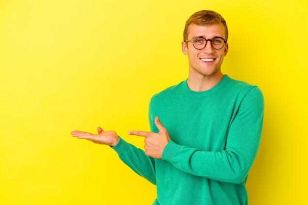 Jeune homme caucasien isolé sur un mur jaune excité tenant un espace de copie sur la paume.