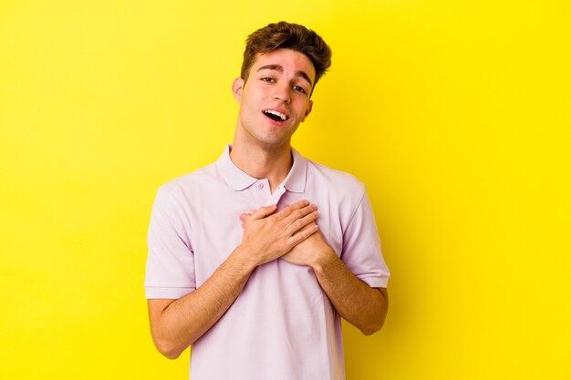 Jeune homme caucasien isolé sur un mur jaune a une expression amicale, en appuyant sur la paume de la main contre la poitrine